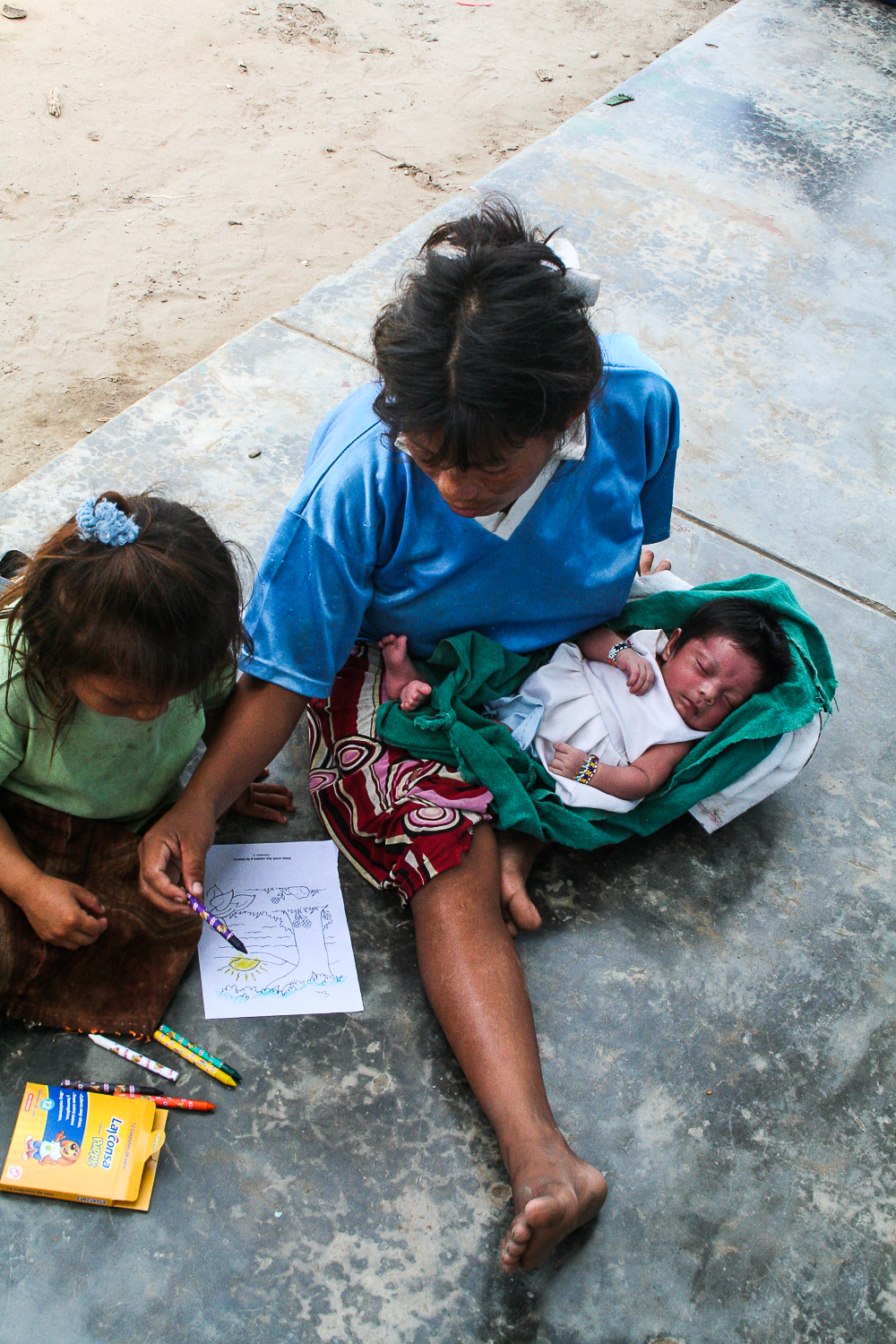 A mother helps her child with a coloring page while her newborn baby sleeps. (Peruvian high jungle)