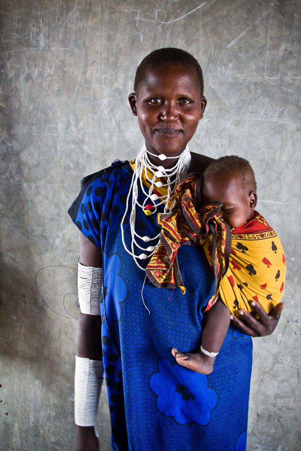 A mother poses with her baby in a school in a rural village in Kenya.