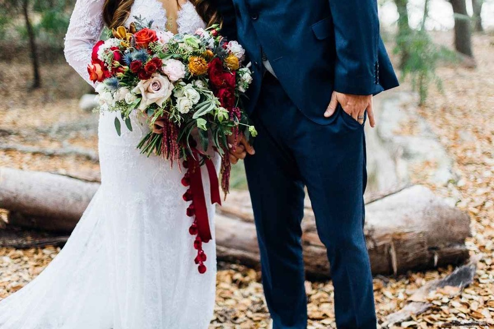 Her bouquet held a mix of garden roses, thistle, orchids, banksia, spray roses, and a ton of greenery. It was absolutely stunning - look at that amazing bauble ribbon!