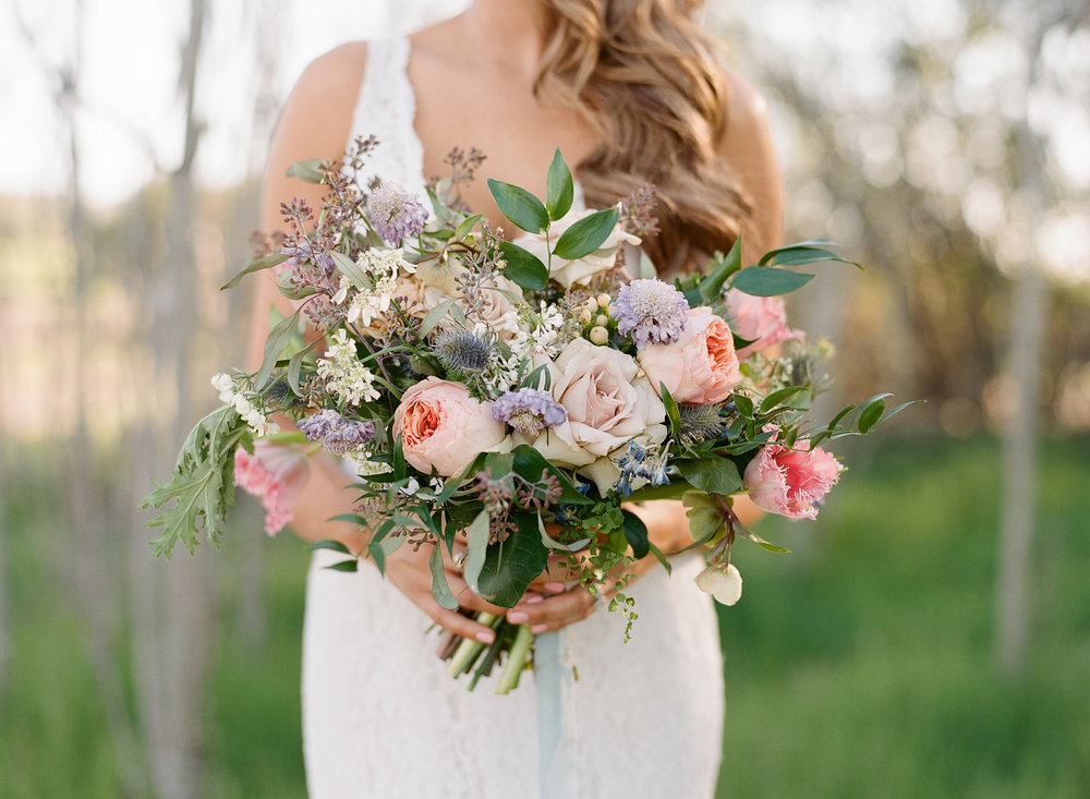 Bridal bouquet using Pantone color inspiration.  Full of peach Juliet roses, Mauve Quicksand roses, blue thistle, pink tulips, lavender scabiosa, eucalyptus, ruscus, fern and more.