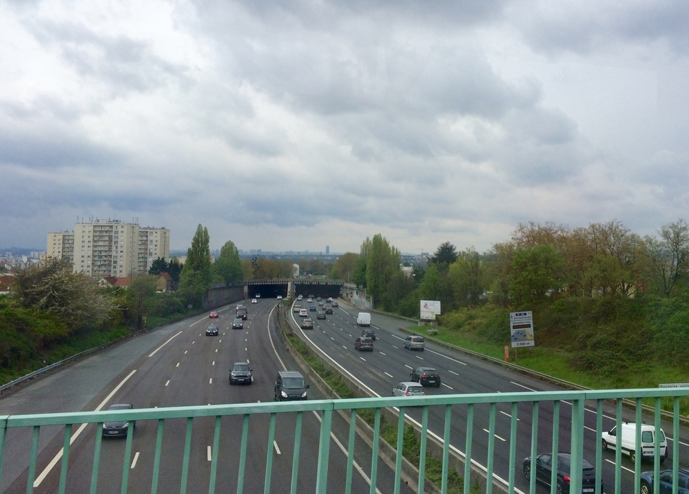 Views of Paris from the overpass. The Eiffel Tower is behind the trees...