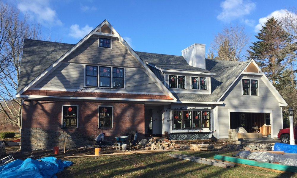 Natural veneer stone being applied to front elevation. New Marvin windows, copper roof detail, cedar shingles and clapboard siding and custom trim details with soffit brackets shown.