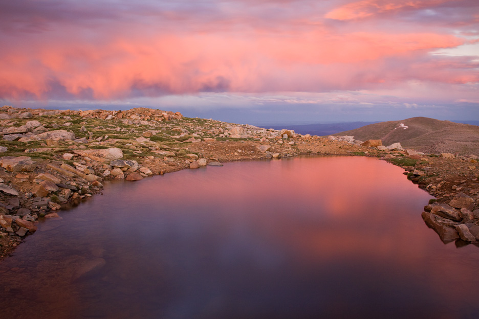 """""""Mt. Evans Sunset"""" - A stormy pink sunset from a small tarn atop Mt. Evans, Colorado."""