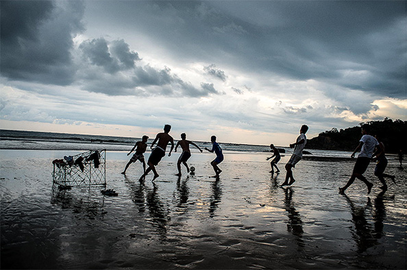 A local soccer team practices on the  beach .