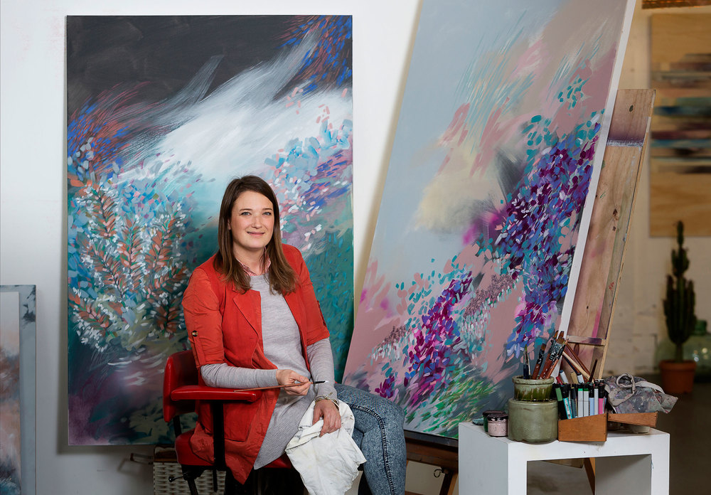 Portrait of Amy Wright in her studio with artworks from the 'Marine Botanicals' series.