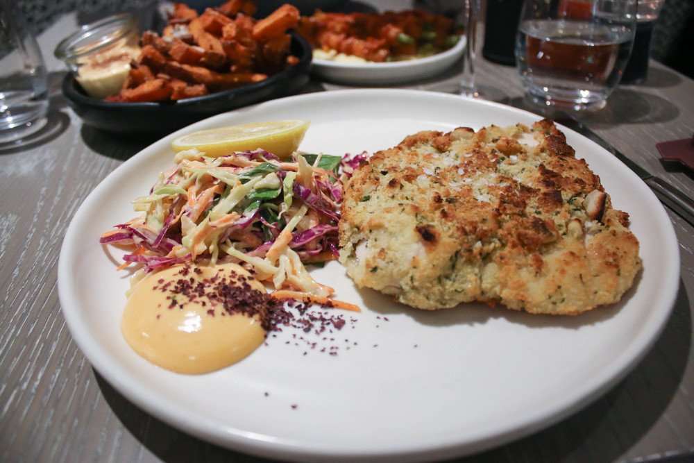 Macadamia Crumbed Chicken Schnitzel with raw salad and sriracha mayo - $27