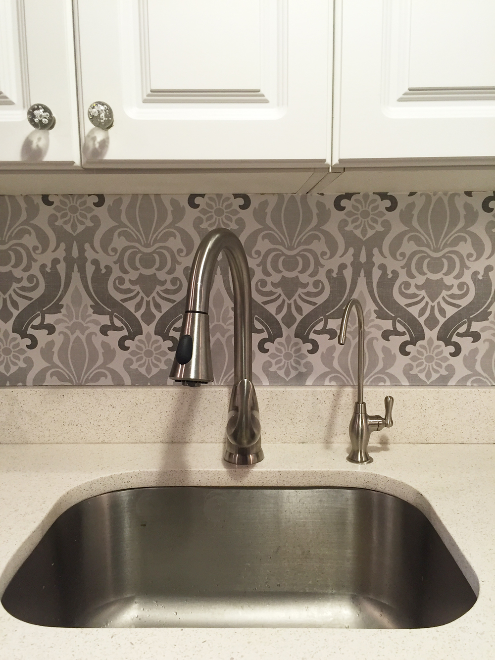 After - I covered the tile with sticky removable wallpaper that can be peeled off when the renter moves. I also changed the silver cabinet knobs with inexpensive glass knobs.