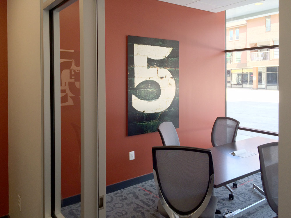 The Business Center has six conference rooms. Each room calls out it's name - One! Two! Three! - by way of oversized, historically sourced typographic numbers on sheets of aluminum.