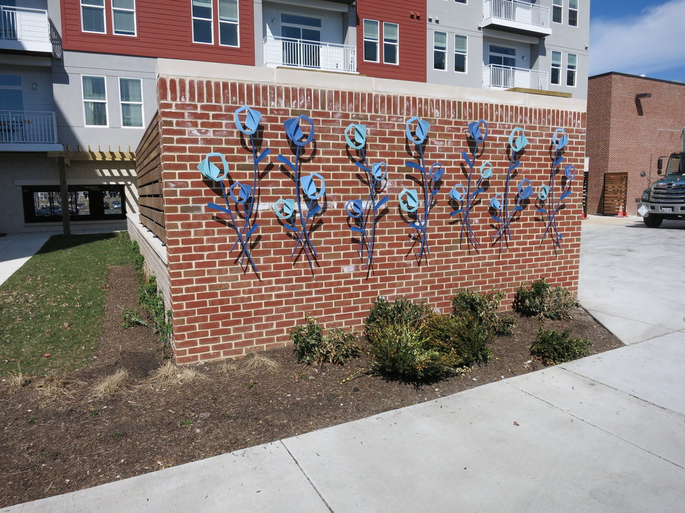 Our installers had to individually mount each welded and powder-coated flower to the brick wall.