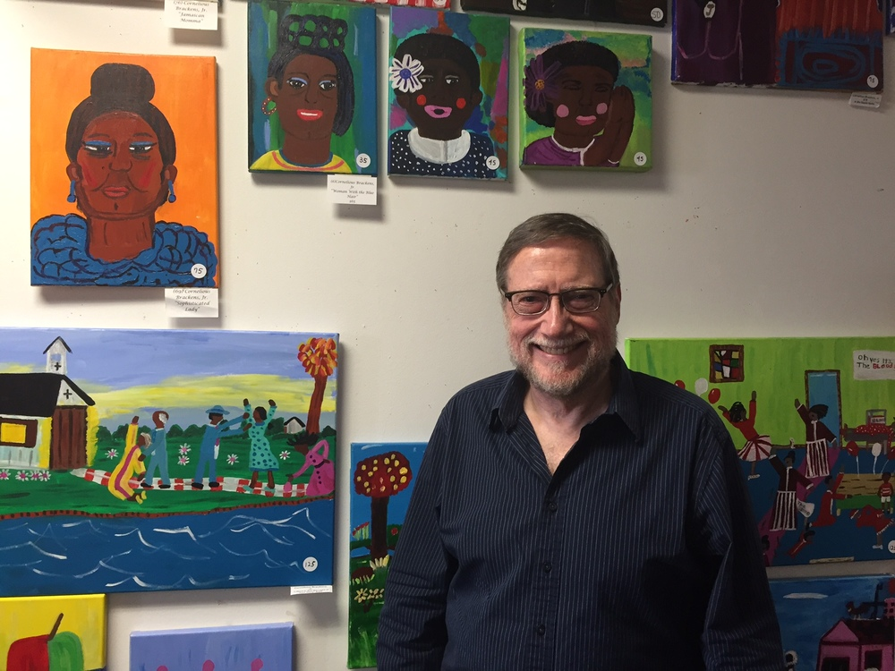Bruce Buchanan, executive director of the Stewpot, stands in front of just some of the art displayed in the homeless center's second-floor gallery. (Hunter Johnson/Staff Contributor)