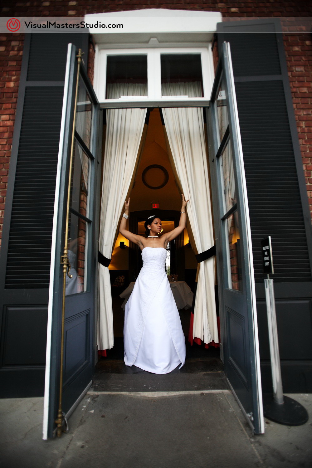 Bride posing by the door by VisualMasters