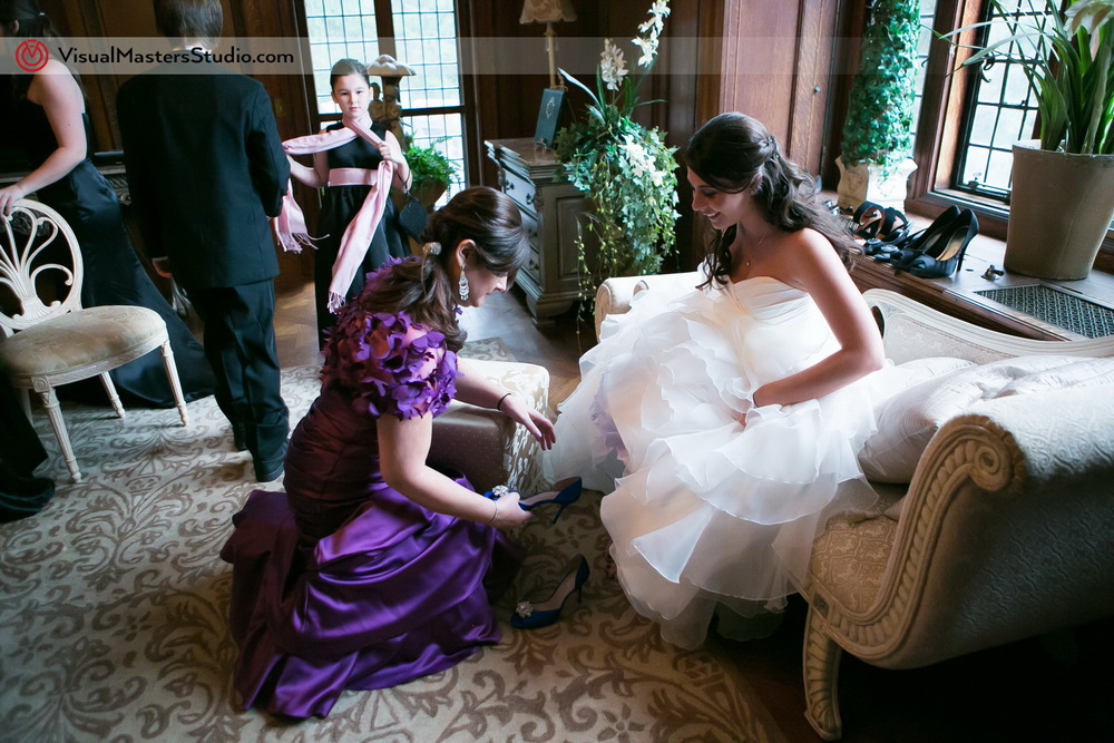 Bride putting on shoes by Visual Masters
