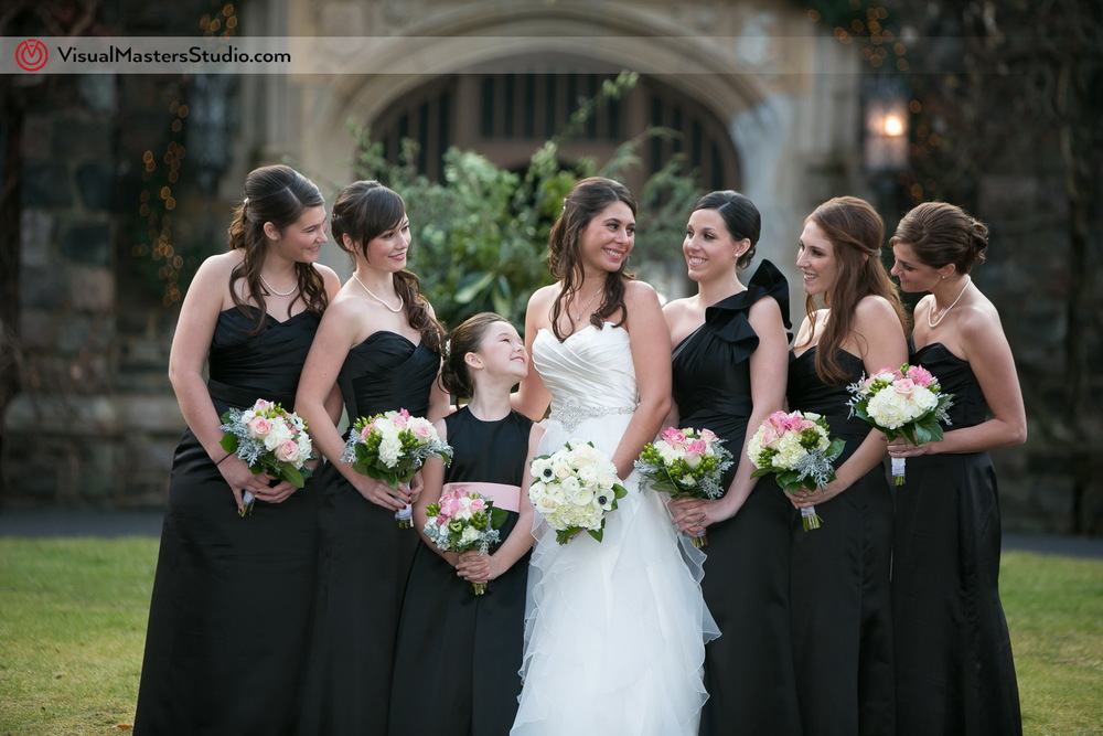 Bride posing with Bridesmaids at The Castle at Skylands Manor by Visual Masters