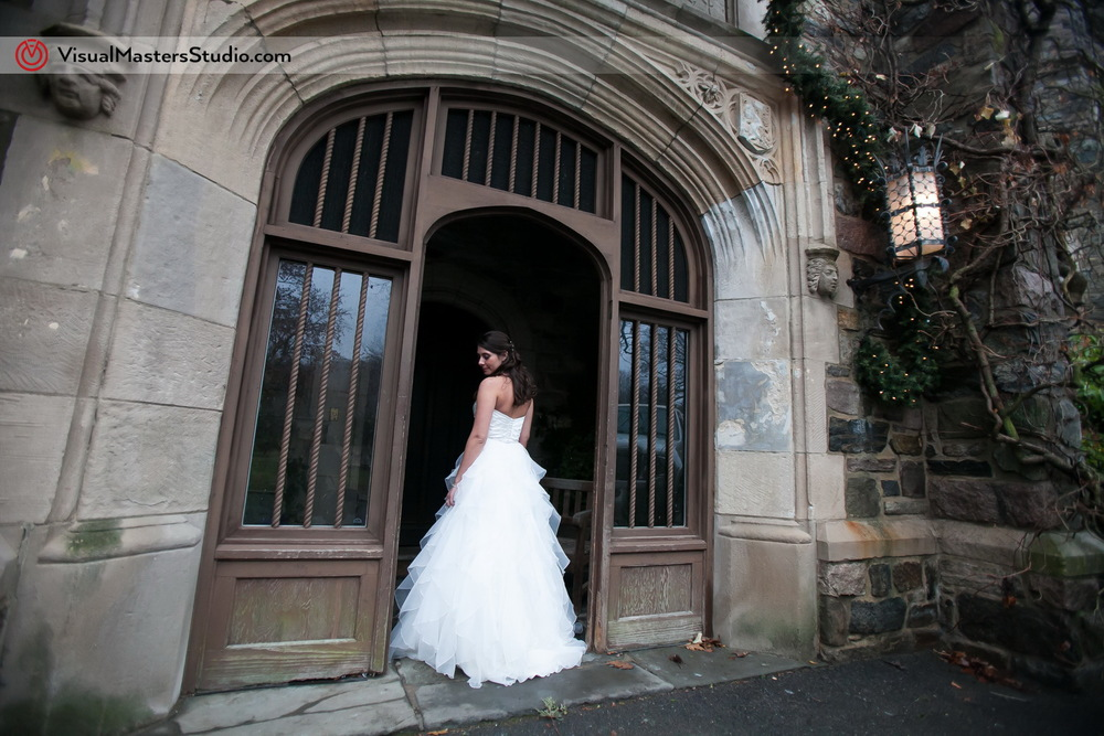 Bride posing at the enterance to at The Castle at Skylands Manor by Visual Masters