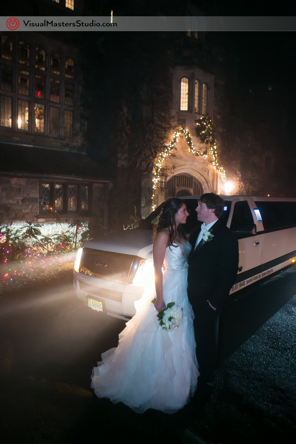 Bride and Groom posing by the limo at The Castle at Skylands Manor by Visual Masters