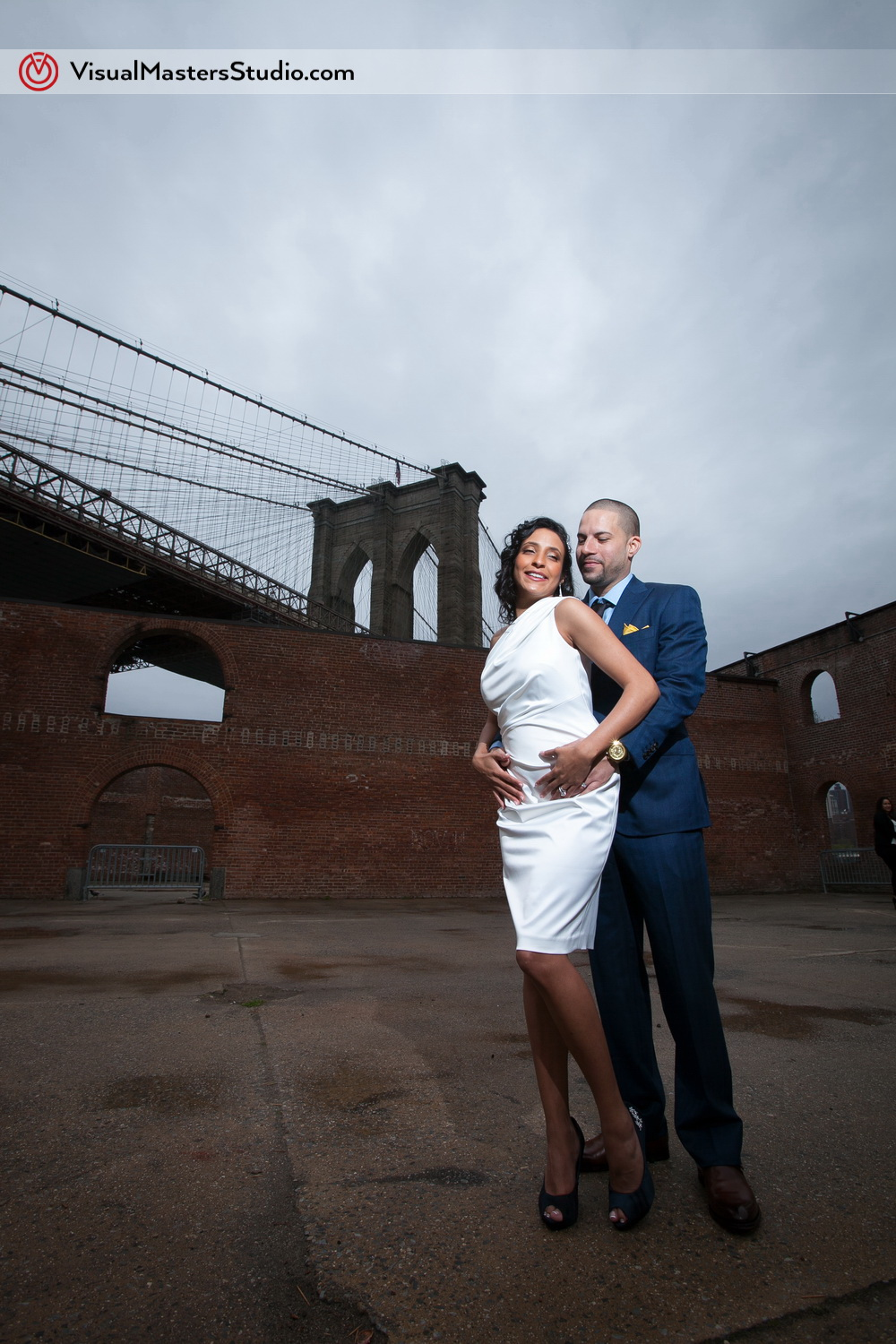 Bride and Groom Posing by Brooklyn Bridge by Visual Masters