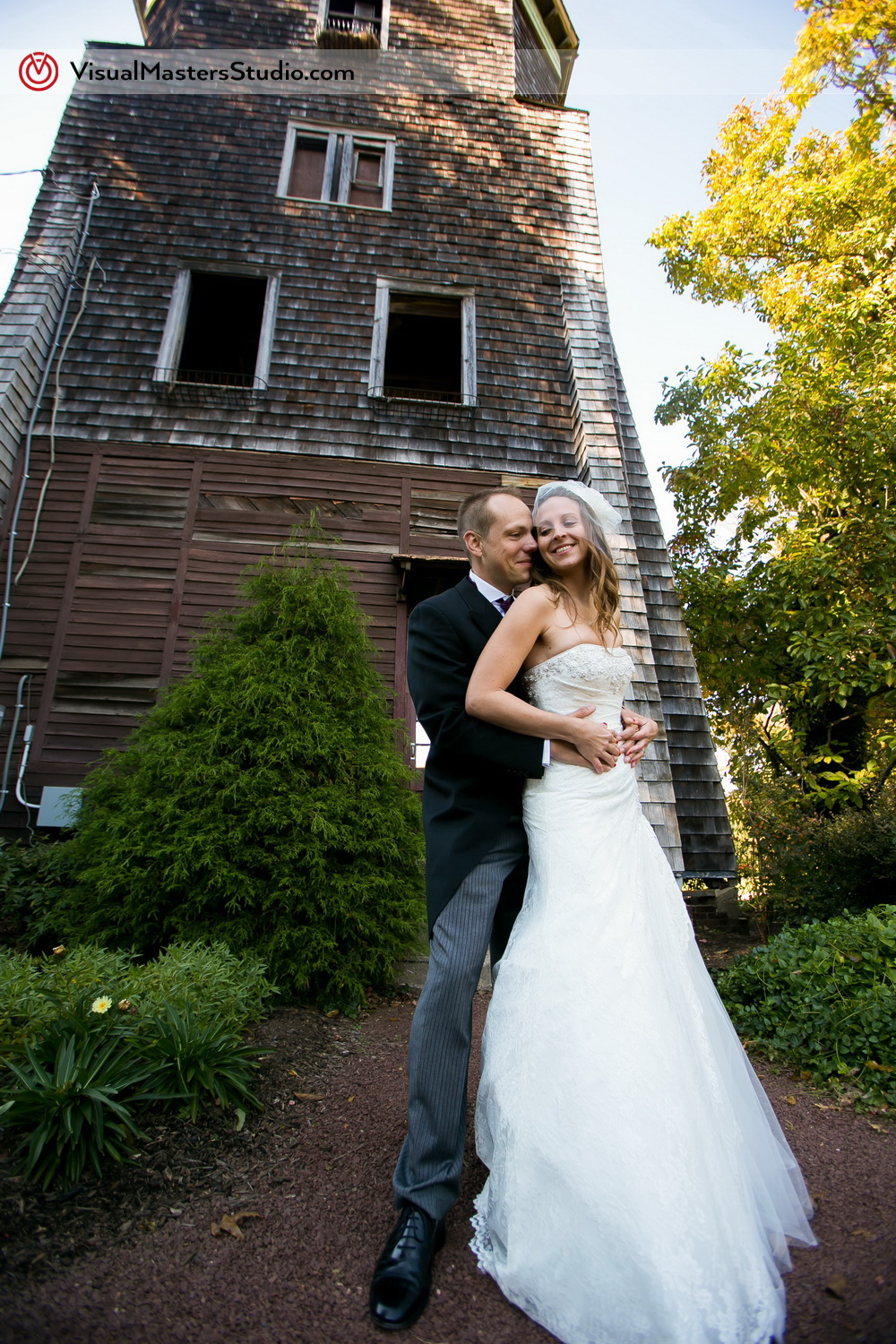 Bride and Groom infront of the Cottage at The Inn at Fernbrook Farms by Visual Masters