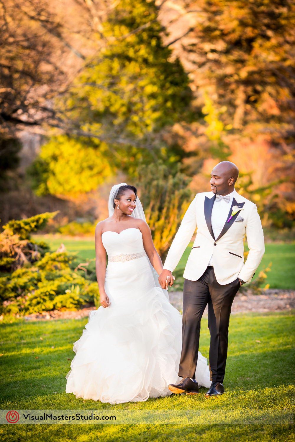 The groom, dressed in a classic tux featuring a white jacket with black collar and silver bow tie, complimented his lovely bride in her sleeveless bride's dress with silver sash.