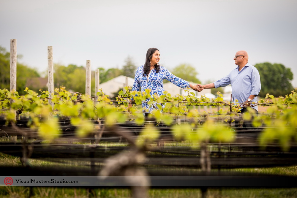Couple walking Trou the Vine Groves at Paunamok Vineyards by Visual Masters