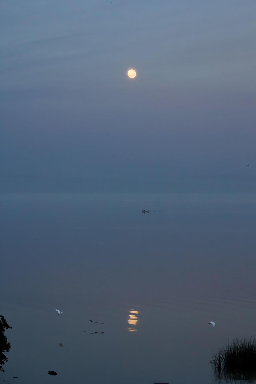 A lua se põe sobre o Guaíba.