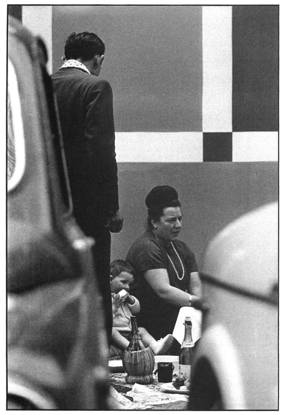Fiera Campionaria, picnic famigliare sul marciapiede tra le auto parcheggiate. Milano, 1964.
