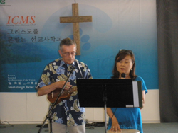 Kay singing a final blessing in Korean on the conferees with Ross accompanying on the ukulele