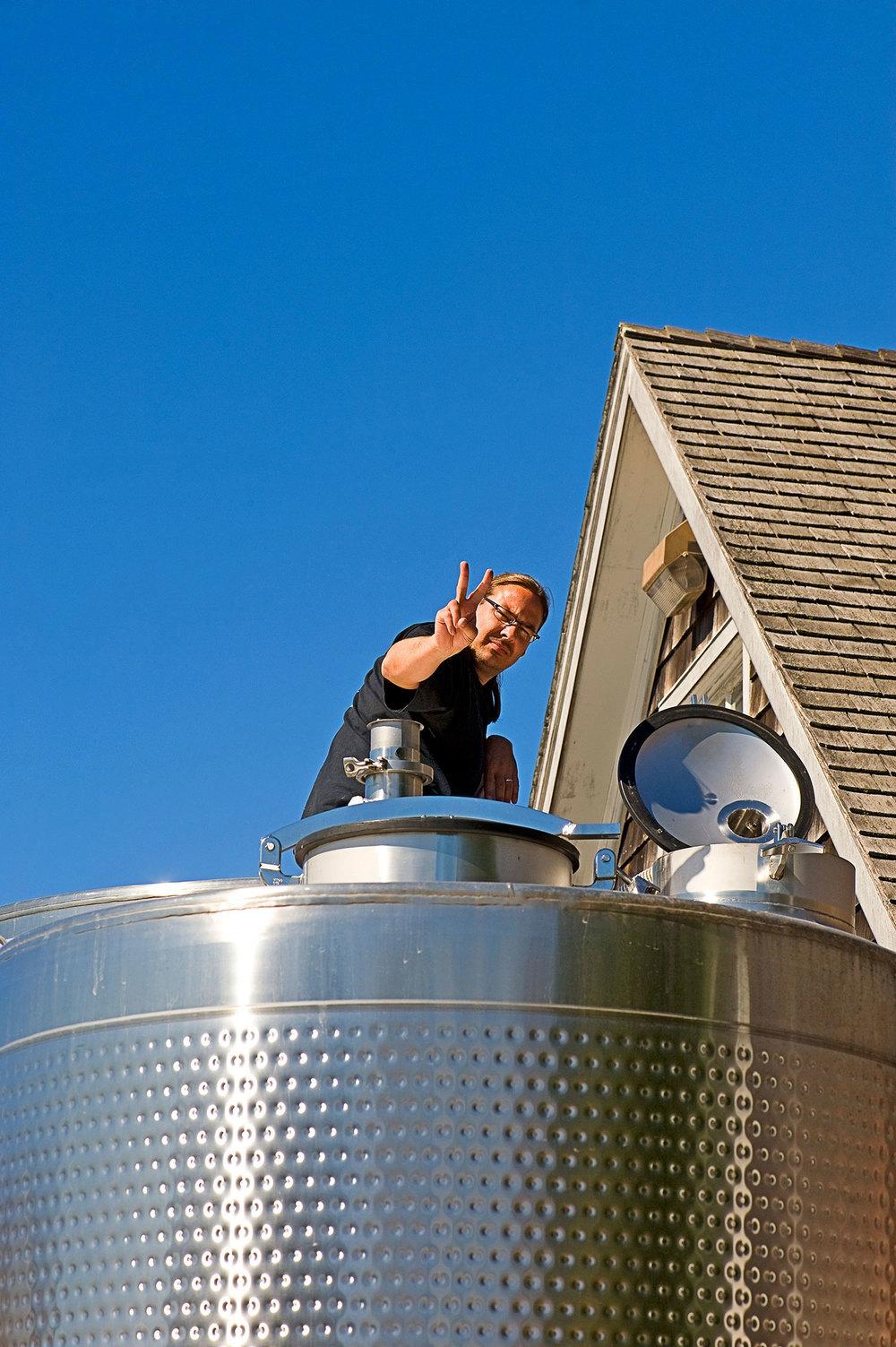 winemaker on top of wine tank