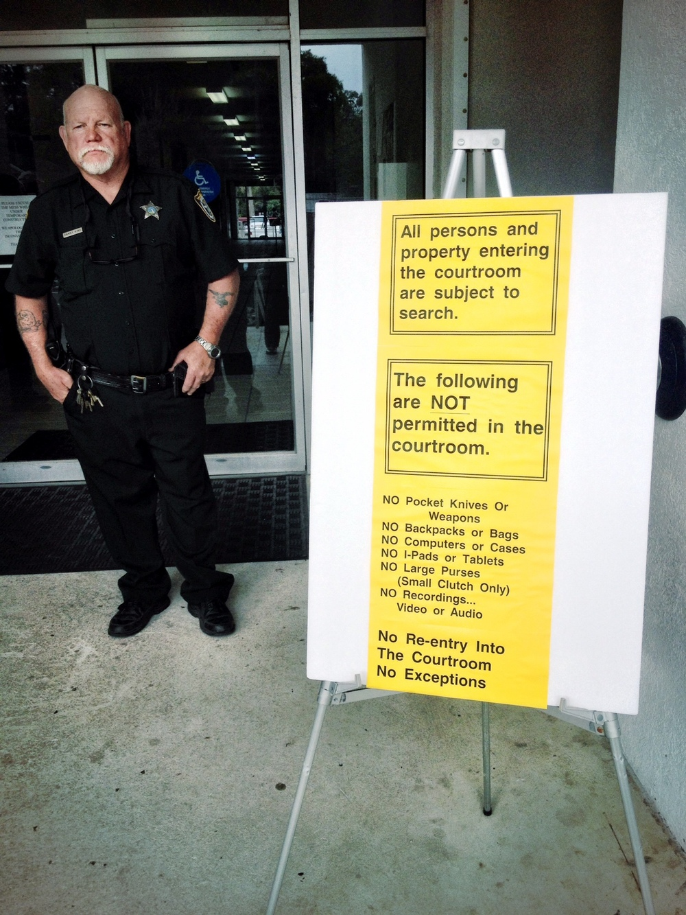 """With the same reply used when rounding up the Jews, Dixie County Deputy ignores the Constitution saying, """"I'm just following orders"""" standing next to a sign before entering their secret society."""