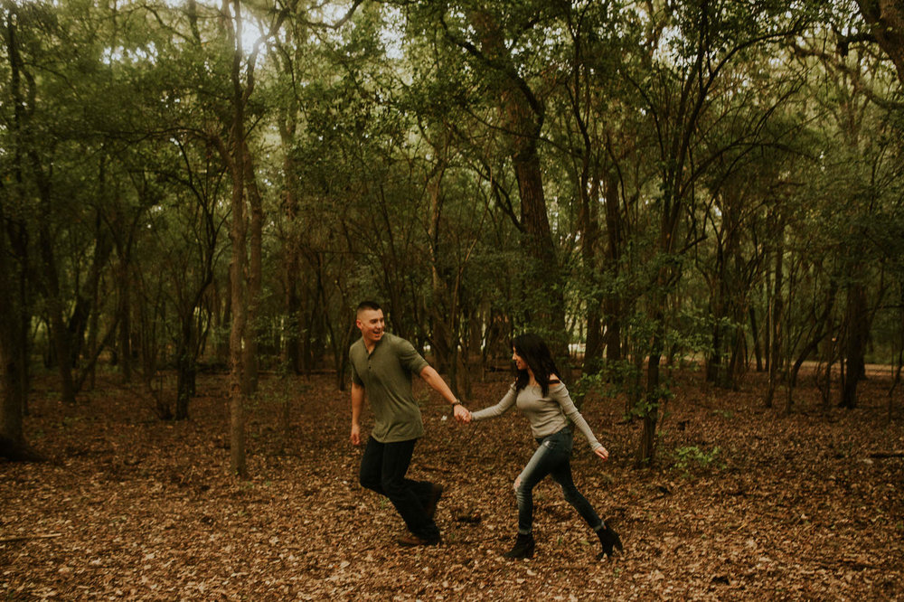 san antonio engagement photography couple running in the woods