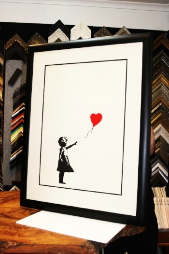 """The Girl with the Red Balloon"" , Banksy.  Preservation framed in our hand finished rounded closed corner profile."