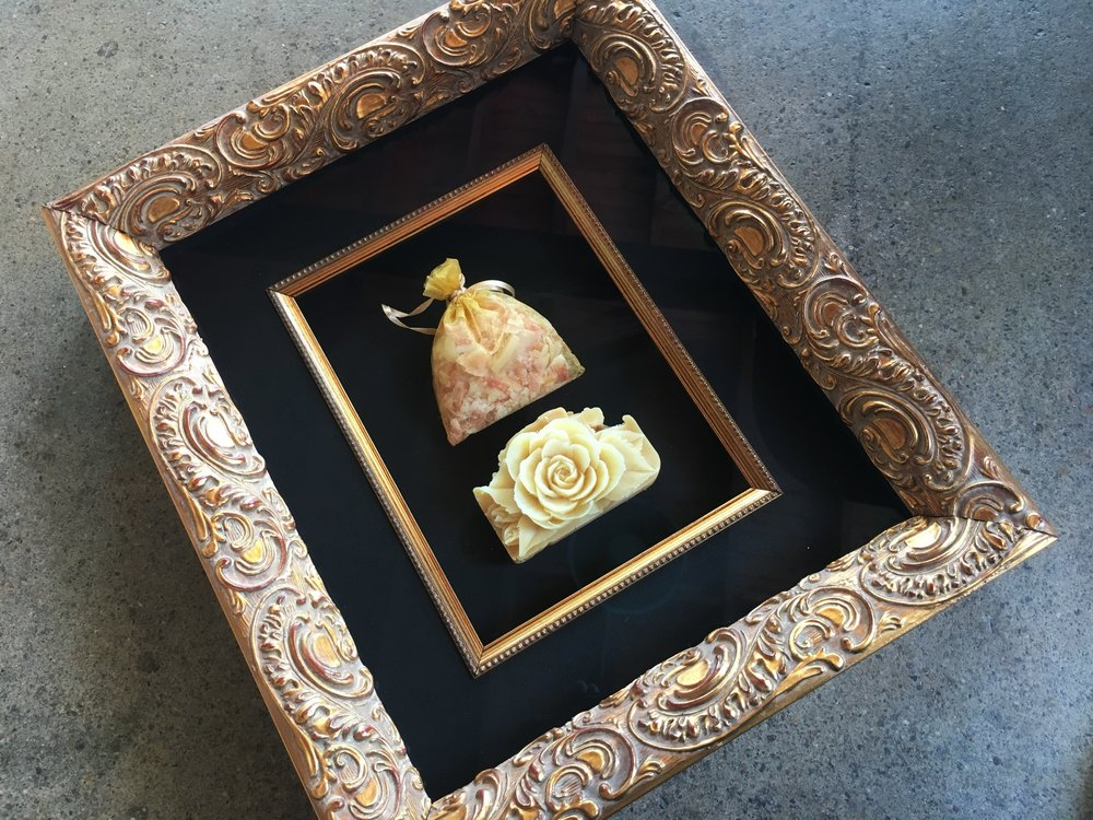 Carved soap framed. Ornate gold frame, black silk matting and a gold fillet trim