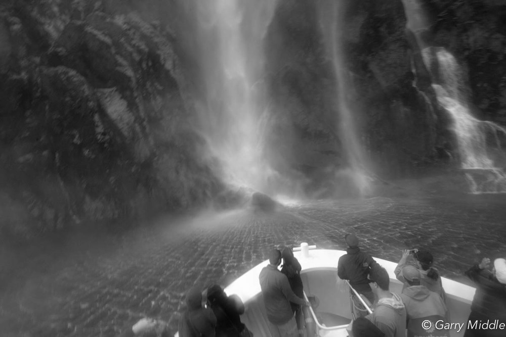 Milford sound waterfall large tourists.jpg