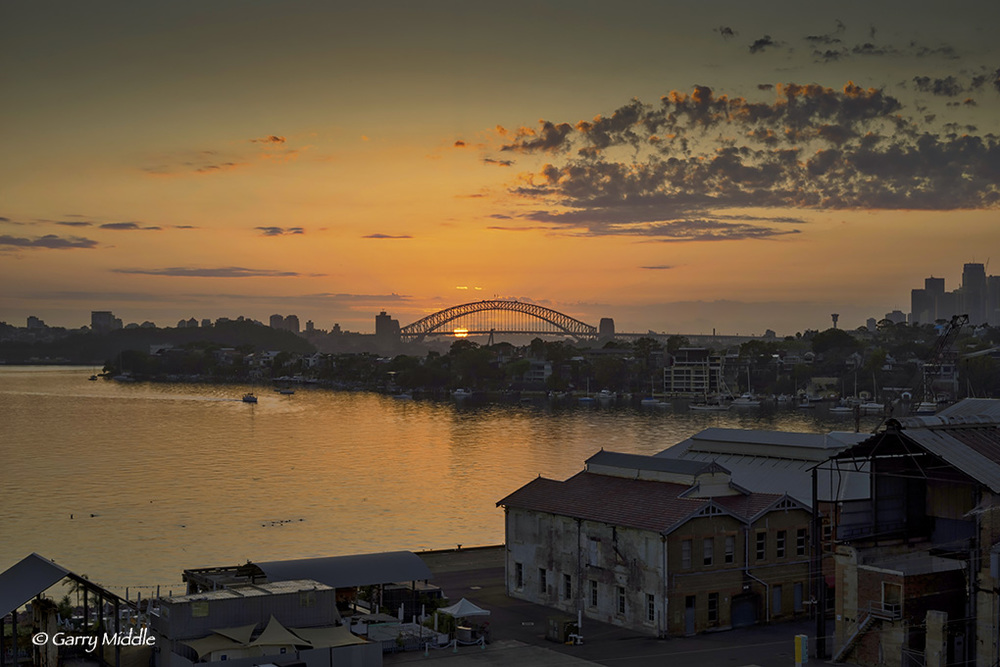 Sunrise through Sydney Harbour bridge.jpg