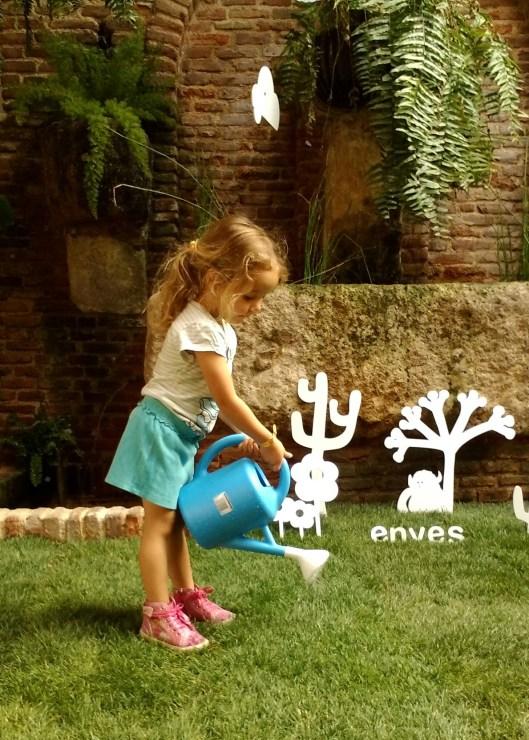 Vega is watering the garden while her mother Pilar running errands.