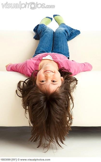 a_girl_hanging_upside_down_from_the_couch_1883099