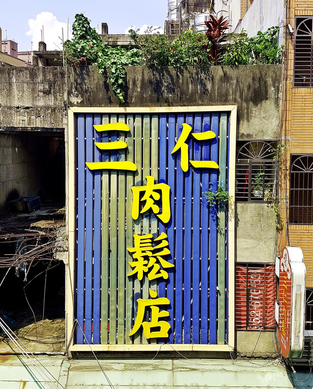 The Sanren Dried Meat Store, an eye-catching sign on a mostly derelict building next to Baohe Temple