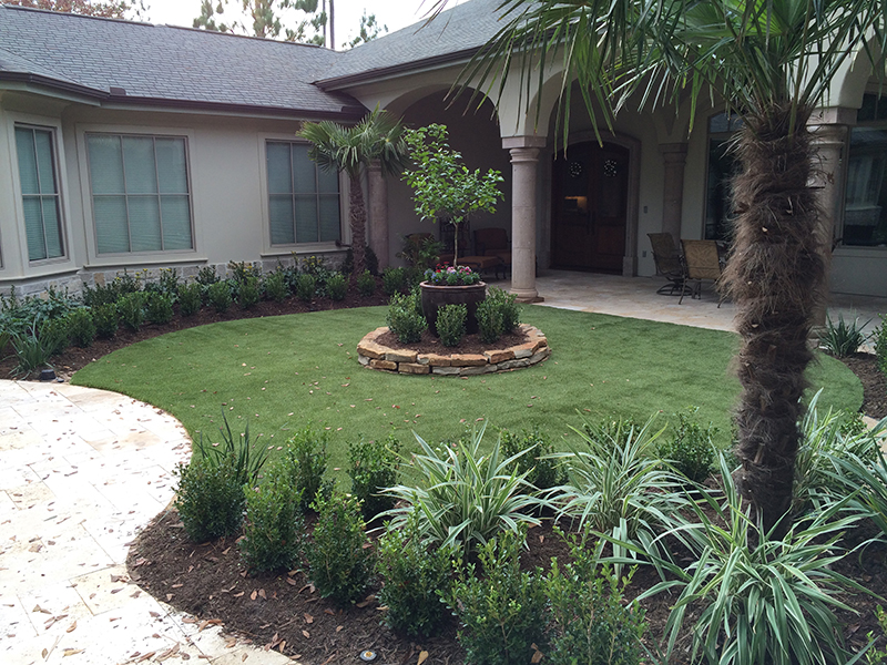 Synthetic-lawn-artificial-turf-courtyard-formal-travertine-The-Woodlands-carlton-woods-travertine-deck-landsacpe-best-maintenance-spring-tx-houston.jpg