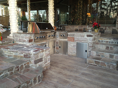outdoor-kitchen-patio-deck-grill-built-in-stone-stamped-concrete-custom-design-covered-new-construction-builder-installation-best-top-company-the-woodlands-spring-cypress-montgomery-carlton-woods-houston-living-luxury-landscape-residential.jpg