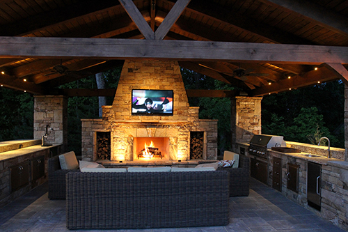 Outdoor-Kitchens-fireplace-cultured-stone-tv-covered-arbor-dark-bbq-stamped-concrete-best-landscaper-builder-the-woodlands-living-houston-spring-cypress-montgomery-traditional-wood.jpg