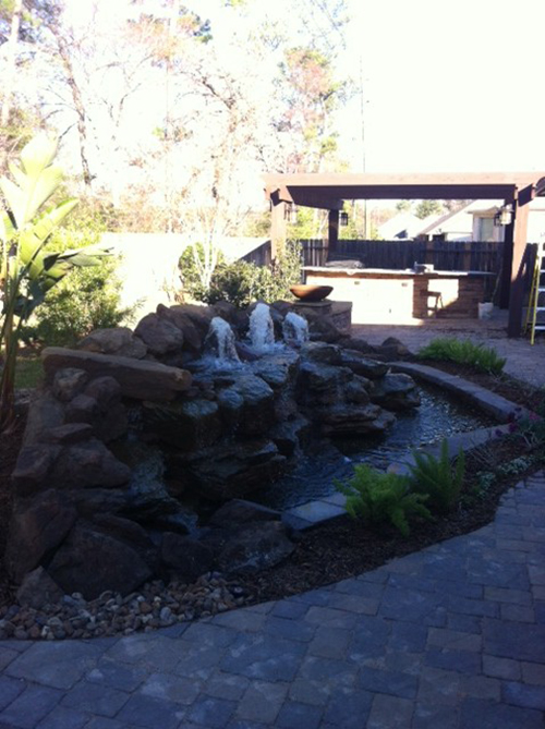 water-feature-water-waterfall-stone-rock-moss-rock-custom-design-paver-patio-beautiful-landscape-best-landscaper-landscaping-ideas-pool-builder-pools-the-woodlands-houston-spring-magnolia-conroe-montgomery-cypress.jpg