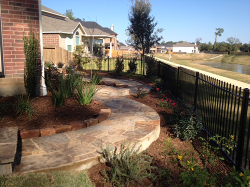 wrought-iron-fence-lake-view-walkway-patioo-decking-stone-design-maintenance-flagstone-installation-installer-aggie-owned-pool-landscaping-the-woodlands-houston-spring-magnolia-conroe-montgomery-cypress.jpg