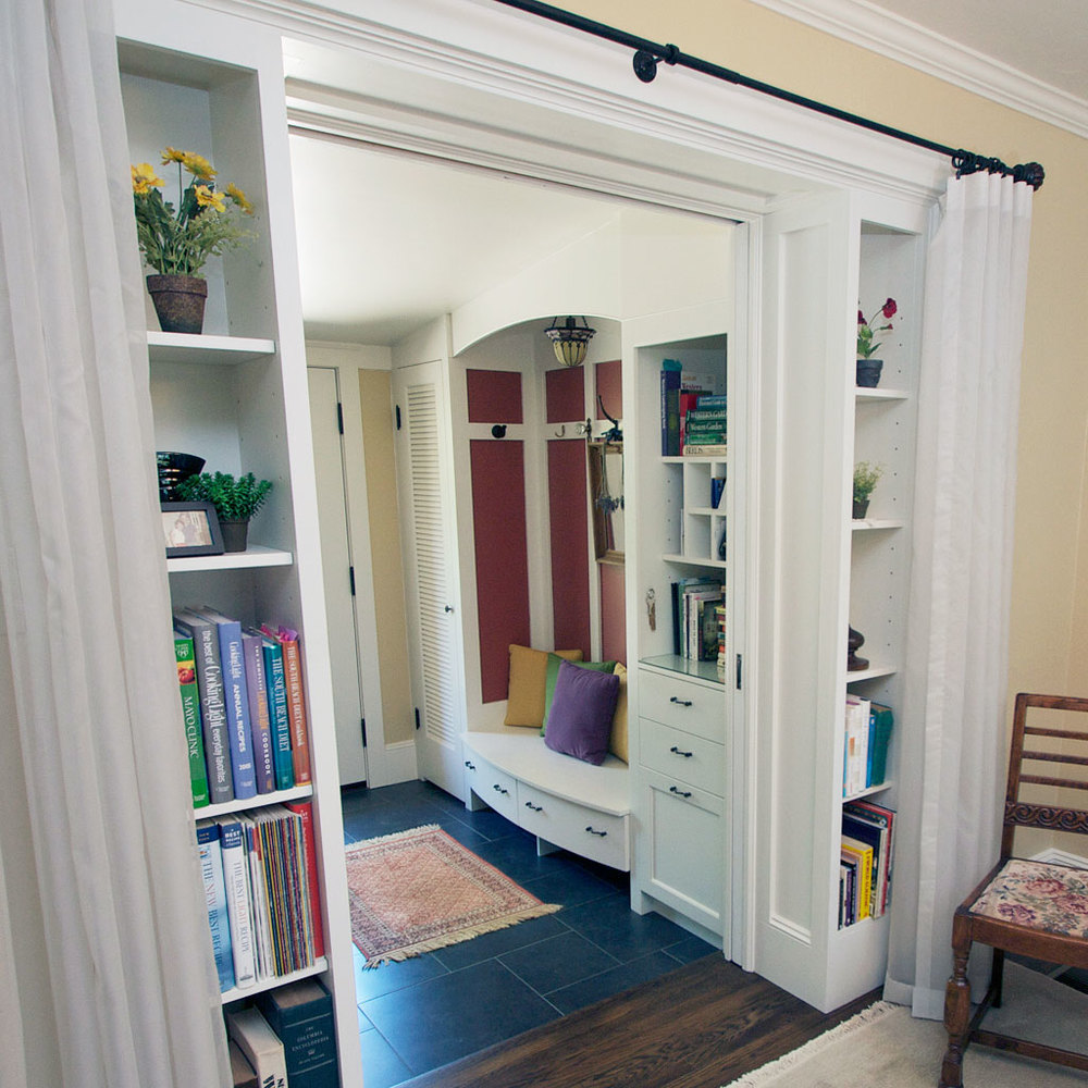 Mudrooms don't have to be ugly or out of site. This wide doorway opens to a view outside. So it's essential the built-ins stay tidy and blend with the woodwork in this Craftsman-inspired home.