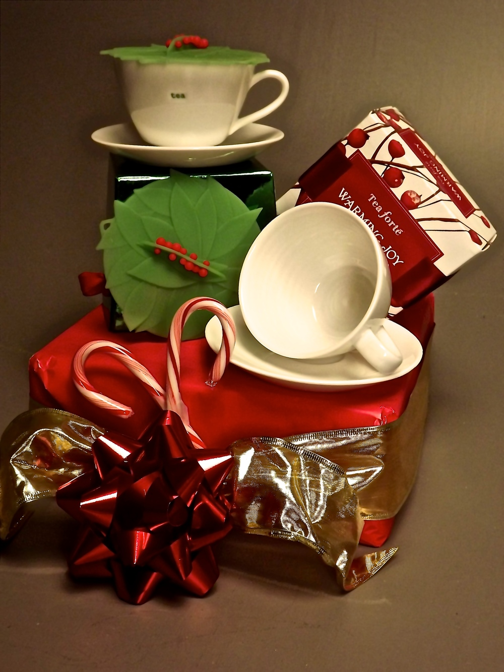 Two teacups & saucers, two holiday beverage covers and a box of tea.