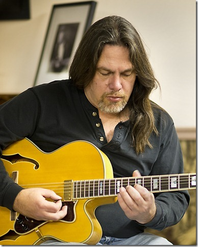 Joesf Glaude educates students at a guitar clinic.