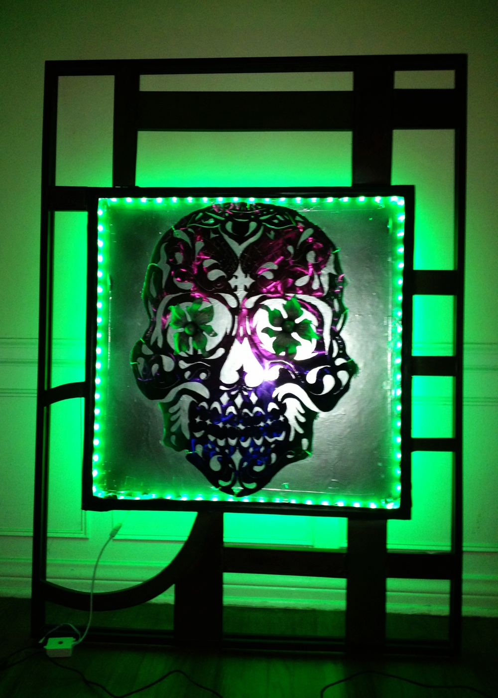 A tribute to Dia De Los Muertos, this sugar skull is adorned with LED work, and found metal materials crafted into a framework around it.