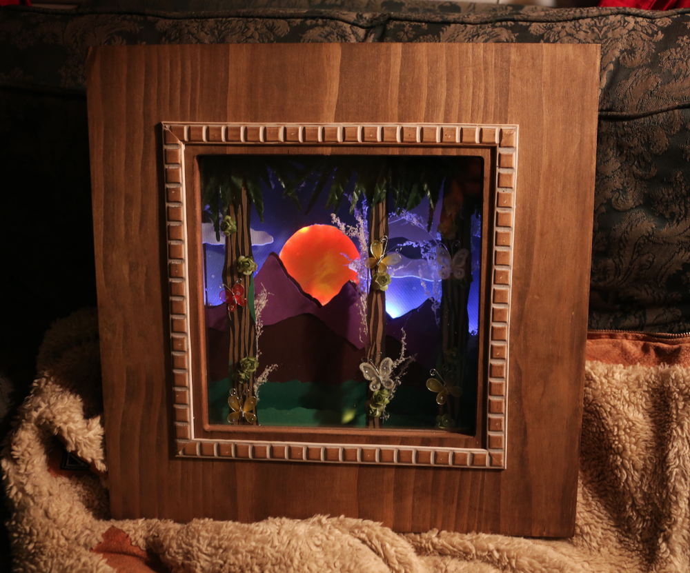 Forest and Mountain Sunset 3-Dimensional Nightlight created for a child's bedroom.  Including three lighting modes to shift the time of day.  Wood, paper, glass, glue, wire, and LEDs.