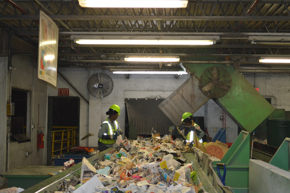 Waste Management employees sort recyclable from non-recyclable materials on a fast-moving conveyor belt.
