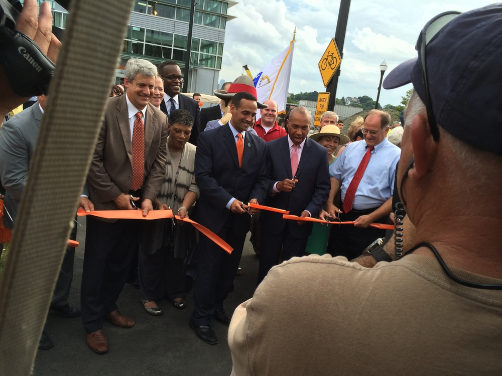 Don Briggs of Federal Realty, Dr. Scott, Curtatone, and Patrick cut the orange tape to symbolically open the station.