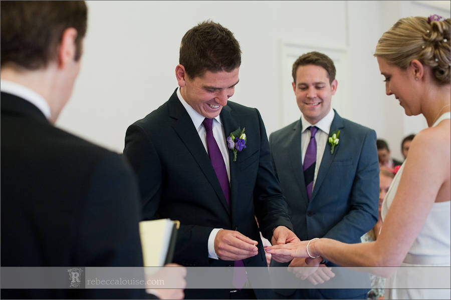 Groom puts ring on bride in Westminster wedding ceremony in Purple Room