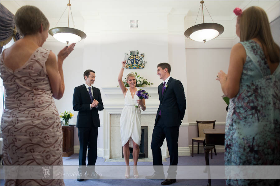 Bride waves wedding certificate after their civil ceremony at Westminster's Purple Room